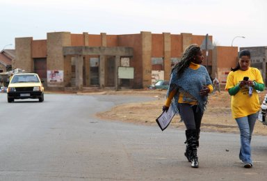 Two women passed the abandoned building behind where Nokuthula Radebe's body was found murdered in March 2011, Thokoza.
